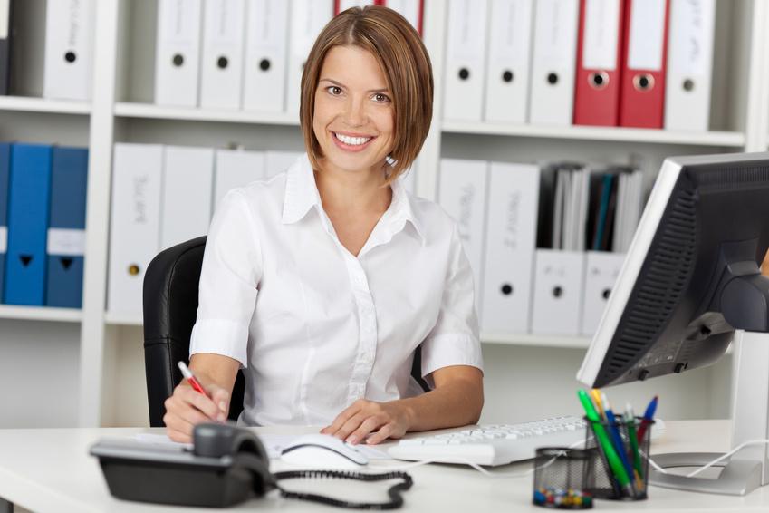 Lachende positiv eingestellte Mitarbeiterin im Büro